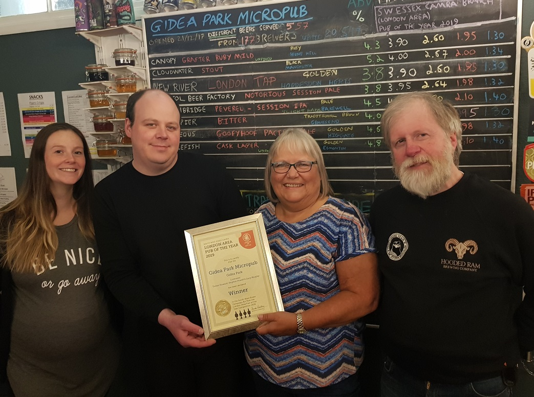Anne holding a framed certificate of the award, with Steve and Trevor on either side of her, and a pregnant Lucy standing next to Steve. They are in front of the board with all the beers written on it, available that day.
