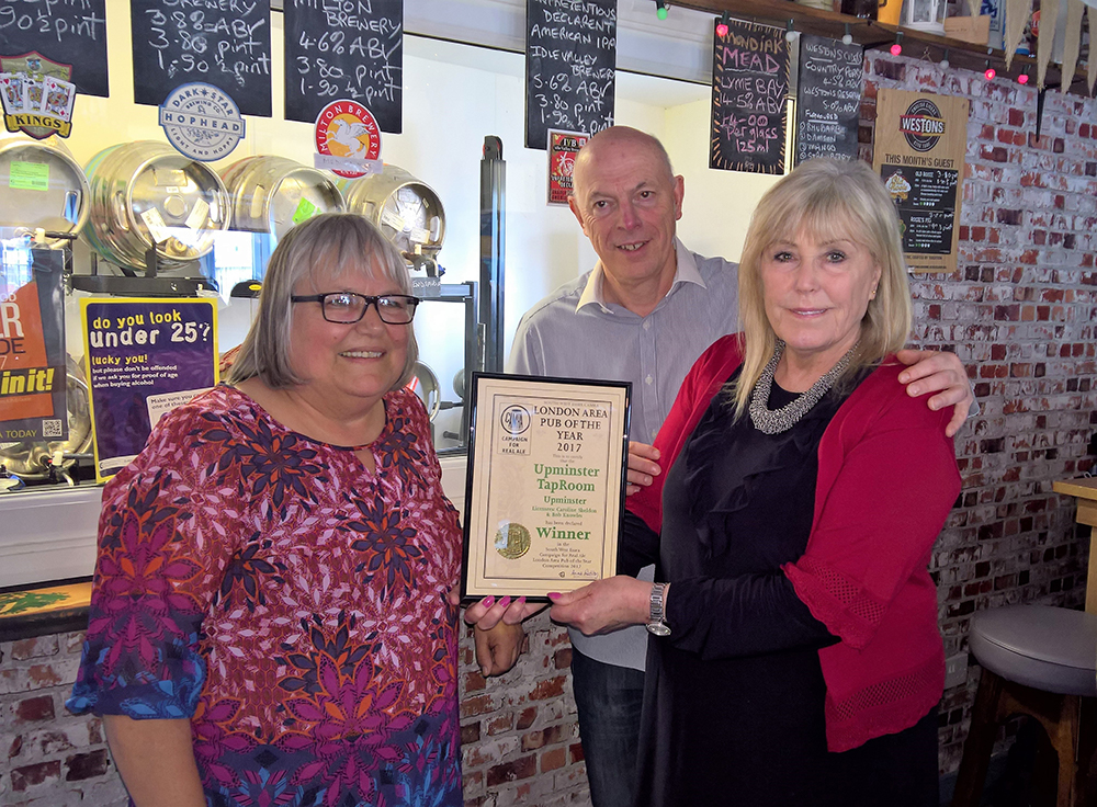 Anne Radley presenting the award to Caroline and Bob at the Upminster Taproom