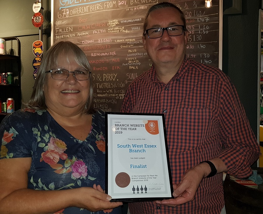 Anne holding a framed certificate of the award, with Steve Hudson to the left of her.