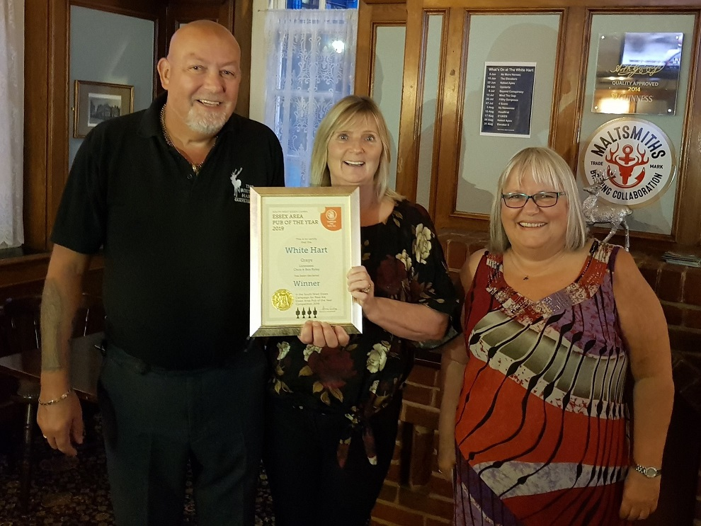 Anne holding a framed certificate of the award, with Ben and Christine to the left of her.
