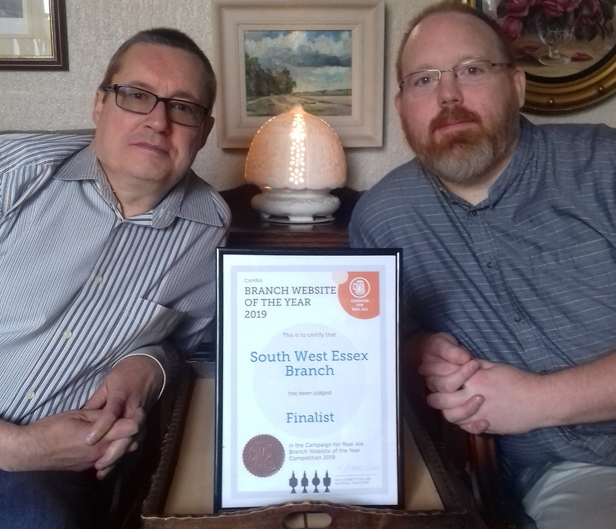 Steve sitting on the right of a framed certificate of the award, with Dean Phillips sat to the left of it.